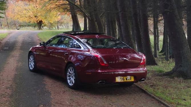 business chauffeur hire Jaguar xjl parked along tree line